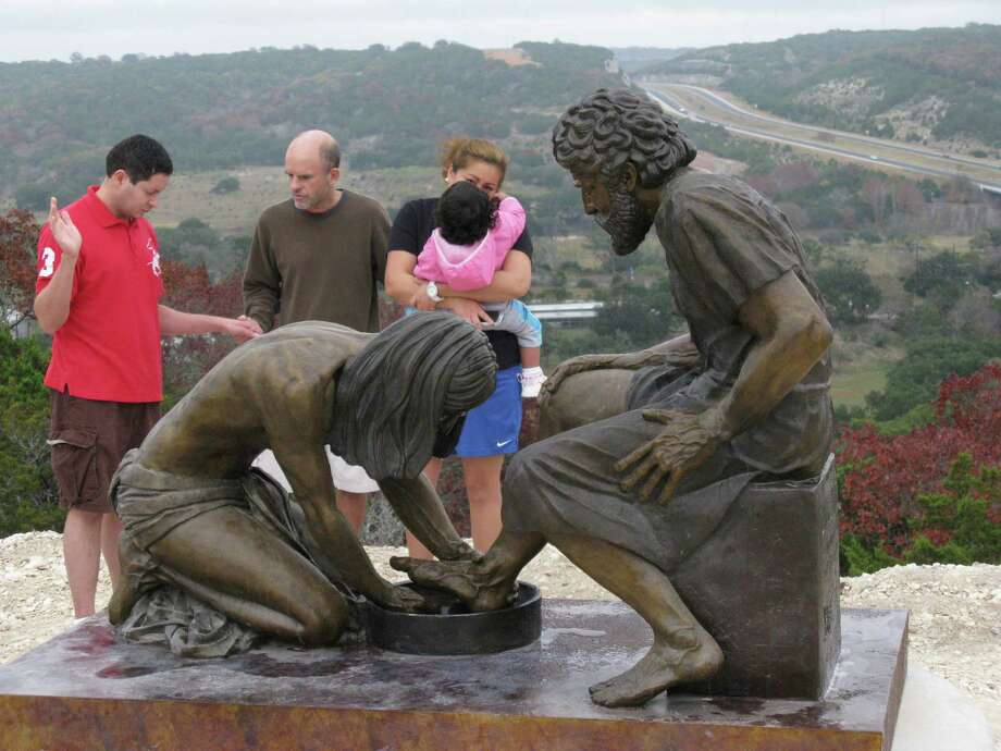 Chris Daniel, center, prays with Luis and Yasmin Sosa and their daughter, Kaylee, beside a sculpture in the Coming King Sculpture Prayer Garden on a hill in Kerrville that overlooks Interstate 10. Daniel is vice president of the nonprofit Coming King Foundation. Photo: Zeke MacCormack / San Antonio Express-News