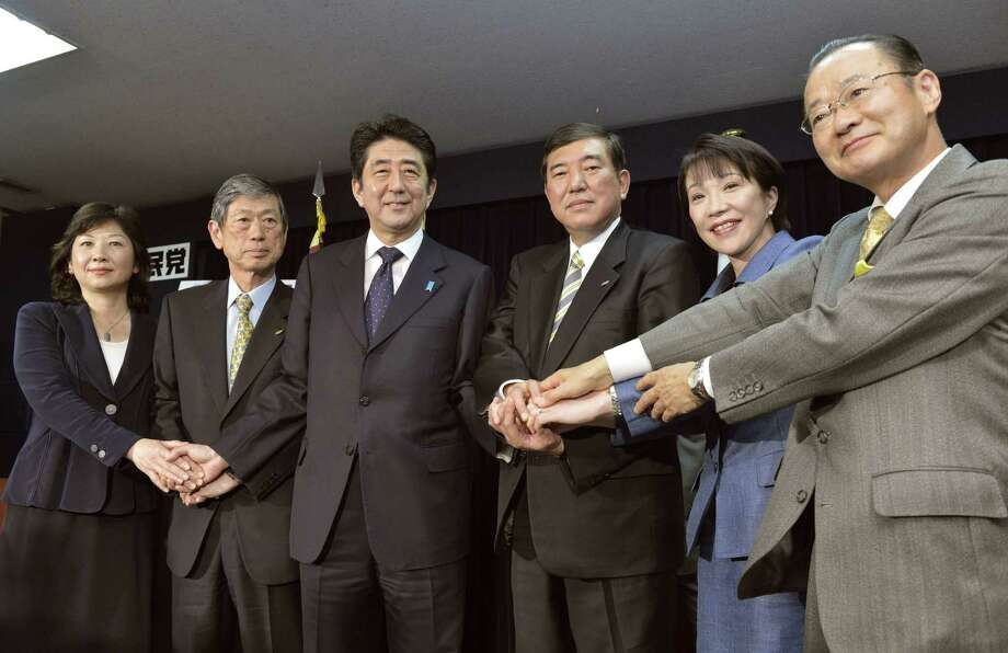Japan's prime-minister-to-be Shinzo Abe, third left, smiles as he joins hands with his top lieutenants Tuesday, Dec. 25, 2012 in Tokyo. Former Prime Minister Abe, who led his conservative Liberal Democratic Party to victory in Dec. 16 elections after three years in opposition, promised his party will pursue fresh policies to tackle the nation's chronic economic woes and bolster its sagging influence on the international stage. The party leaders are from left:  General Council Chairman Seiko Noda, Vice-President Masahiro Komura, Abe, Secretary-General Shigeru Ishiba, Policy Research Council Chairman Sanae Takaichi and Election Strategy Headquarters head Takeo Kawamura. (AP Photo/Kyodo News) JAPAN OUT, MANDATORY CREDIT, NO LICENSING IN CHINA, HONG KONG, JAPAN, SOUTH KOREA AND FRANCE