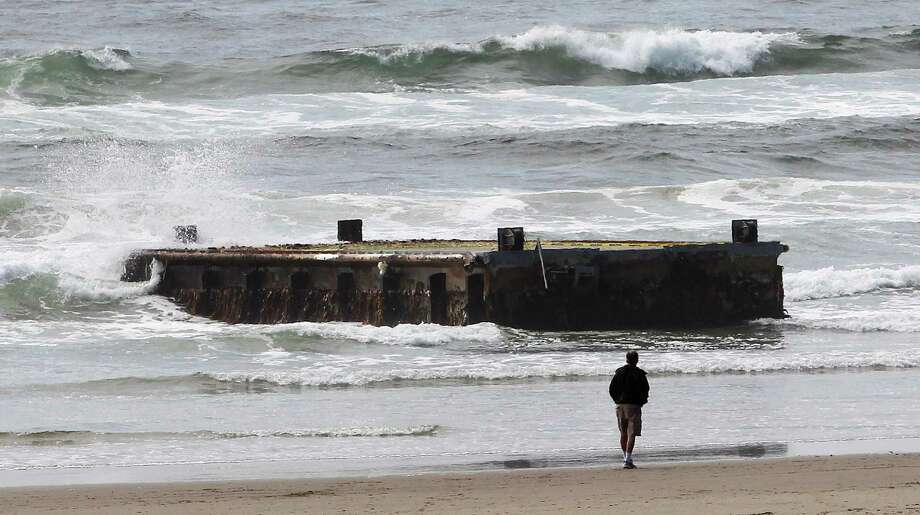 FILE -In this file photo from Wednesday, June 6, 2012, a man looks at a 70-foot-long dock with Japanese lettering that washed ashore on Agate Beach in Newport, Ore. The West Coast is anticipating more debris from the 2011 Japanese tsunami to wash ashore this winter. Scientists expect the bulk of the tsunami debris to end up in the Pacific Northwest. (AP Photo/Rick Bowmer, File) Photo: Rick Bowmer