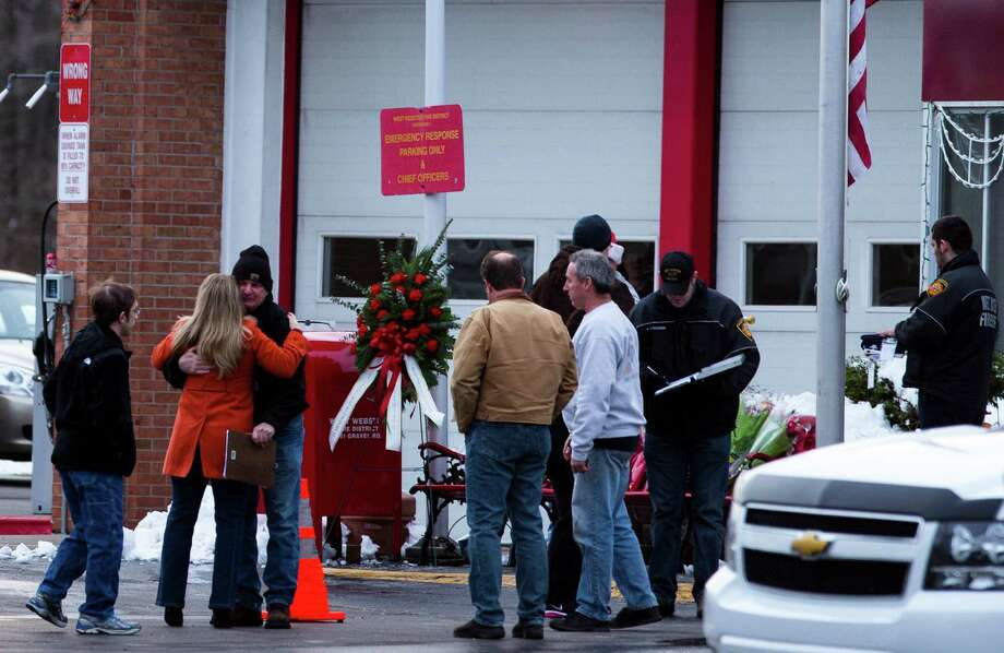 People gather near a makeshift memorial at the West Webster Fire Department for firefighters killed while responding to a fire in Webster, N.Y., Dec. 24, 2012. Two firefighters were killed and two were shot but survived while responding to a blaze where the suspected assailant also died of a self-inflicted wound, officials said. (Brett Carlsen/The New York Times) Photo: BRETT CARLSEN / NYTNS