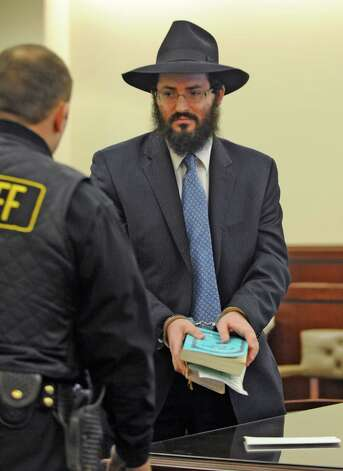 Rabbi Yaakov Weiss, formerly of Chabad of Colonie holds his prayer books and wears handcuffs after being sentenced to 60 days in Albany County Jail, his sentence for child endangerment in from Judge Stephen Herrick at the Albany County Judicial Center in Albany, New York March 8, 2010.         (Skip Dickstein/Times Union) Photo: Skip Dickstein / 00007788A