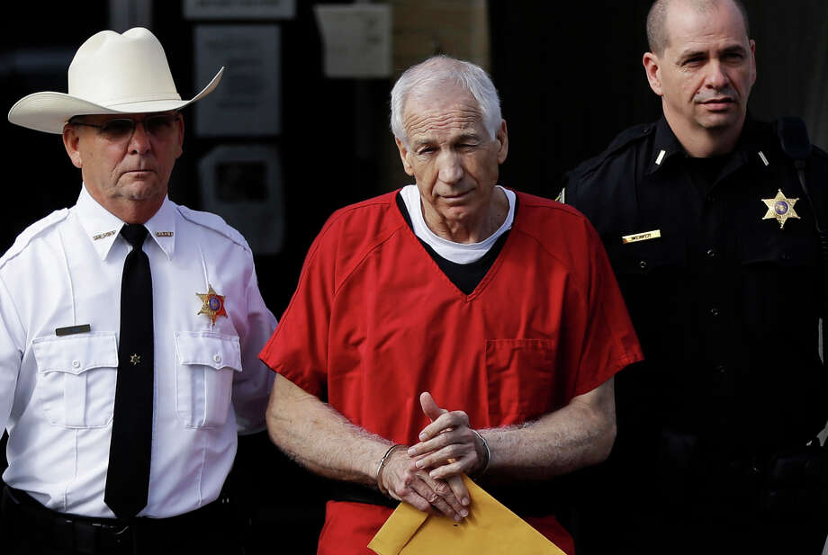 FILE - In this Oct. 9, 2012 file photo, former Penn State University assistant football coach Jerry Sandusky, center, is taken from the Centre County Courthouse by Centre County Sheriff Denny Nau, left, and a deputy, after being sentenced in Bellefonte, Pa. Sandusky was sentenced to at least 30 years in prison, effectively a life sentence, in the child sexual abuse scandal that brought shame to Penn State and led to coach Joe Paterno's downfall. The Sandusky saga was a top story in the sports world in 2012. (AP Photo/Matt Rourke, File) Photo: Matt Rourke