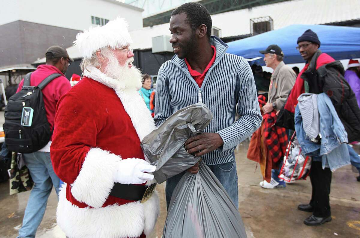 A man dressed as Santa listens while Antonio Jackson tells him thank you for helping him bag clothes he was given at The Extended Aftercare Alumni event on Christmas morning in downtown Houston. Volunteers distributed a holiday meal, clothes, and hygiene gift packages on Christmas morning in a holiday tradition started to give people new to recovery from drug and alcohol addiction an opportunity to be of service.