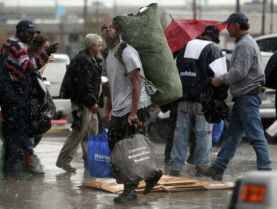Al Horne looks up at the rain falling on homeless people waiting in line to receive a Christmas meal by The Extended Aftercare Alumni volunteers on Christmas morning in downtown Houston. Photo: Mayra Beltran, Houston Chronicle / © 2012 Houston Chronicle