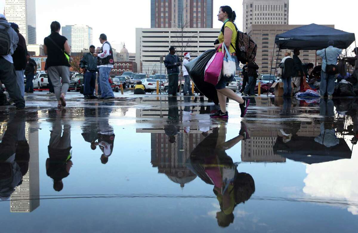 Evelyn Anness is reflected in puddles left by a passing storm as she walks with her arms full of items and free clothing at the Extended Aftercare Alumni holiday event in downtown Houston. Volunteers distributed a holiday meal, clothes, and hygiene gift packages on Christmas morning.