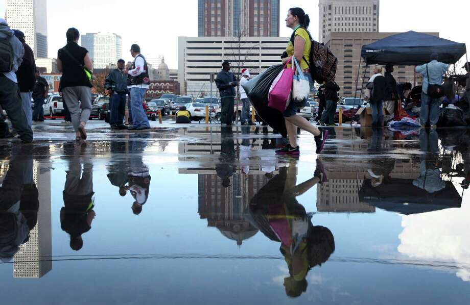 Evelyn Anness is reflected in puddles left by a passing storm as she walks with her arms full of items and free clothing at the Extended Aftercare Alumni holiday event in downtown Houston.   Volunteers distributed a holiday meal, clothes, and hygiene gift packages on Christmas morning. Photo: Mayra Beltran, Houston Chronicle / © 2012 Houston Chronicle