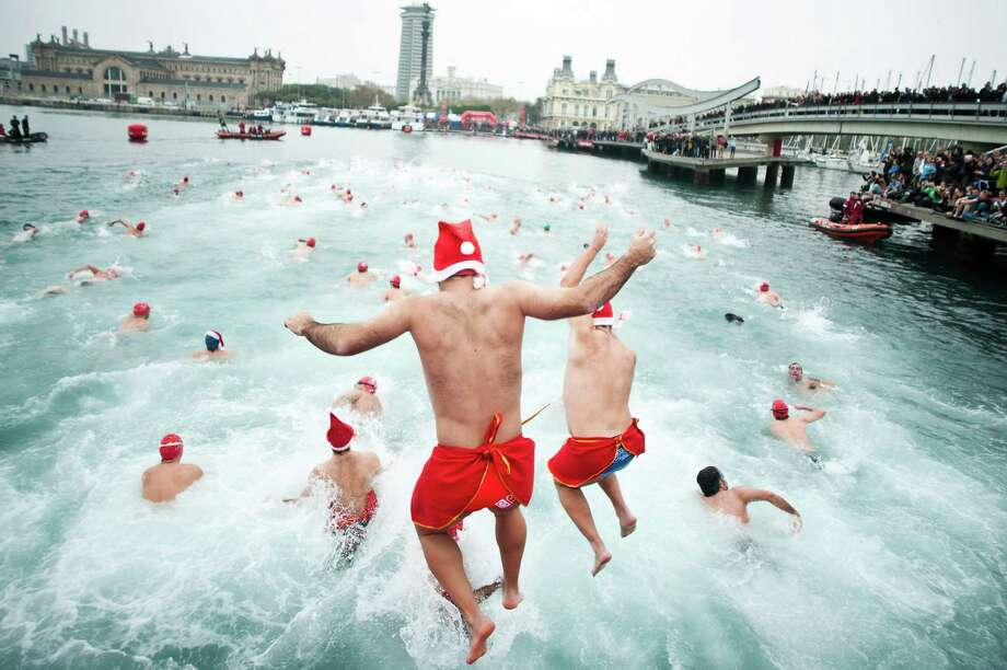 Competitors jump into the sea during the 103rd Barcelona Traditional Christmas Swimming Cup at the Old Harbour of Barcelona on December 25, 2012 in Barcelona, Spain. The Copa Nadal is organised by the Barcelona Swimming Club and involves competitors swimming across some 200 metres of water in the harbour. Launched in 1908 the event has only been suspended three times when the Spanish Civil War interrupted proceedings between 1936 and 1938. Photo: David Ramos, Getty Images / 2012 Getty Images