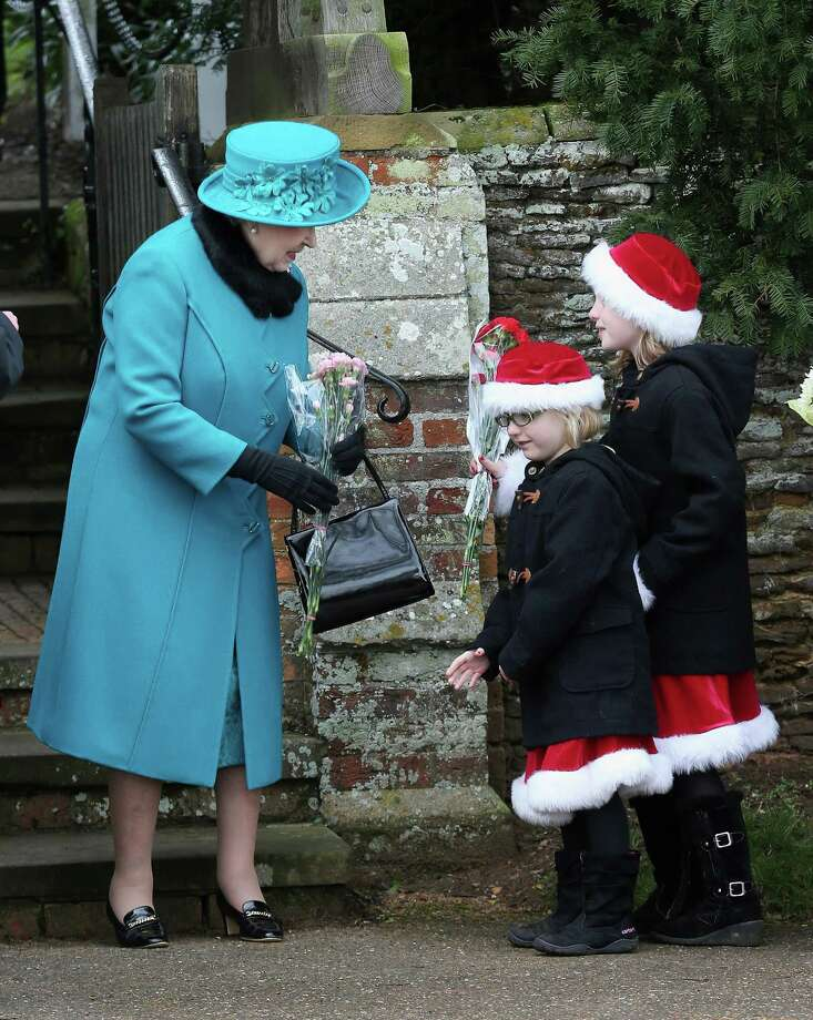 Queen Elizabeth II is presented with flowers by two girls wearing Santa outfits as she leaves St Mary Magdalene Church after attending the traditional Christmas Day church service on December 25, 2012 in Sandringham near King's Lynn, England. Photo: Chris Jackson, Getty Images / 2012 Getty Images