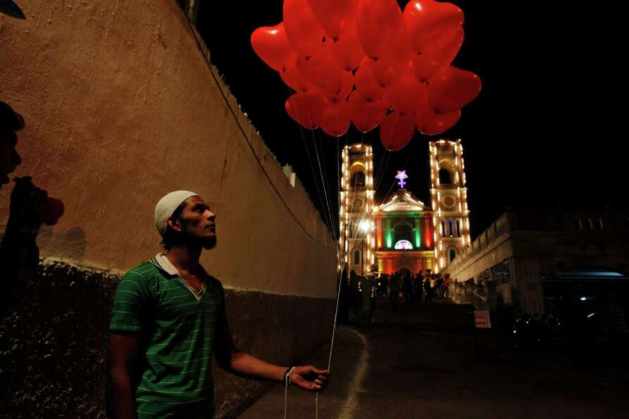 An Indian Muslim vendor sells balloons in front of St Joseph Cathedral during Christmas celebrations
