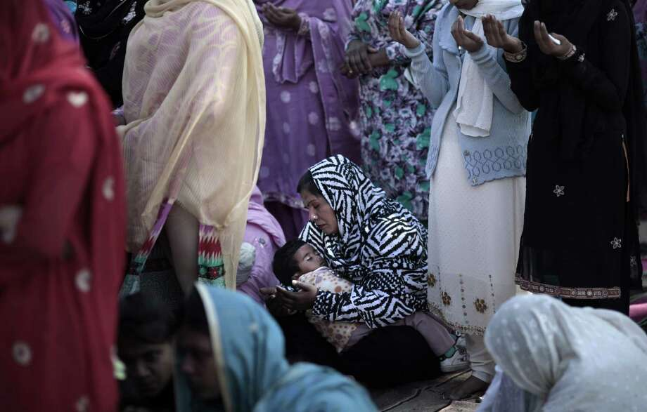 A Pakistani child, center, sleeps on her mother's lap, while she and other women pray during an outdoor Mass on Christmas Day, in a Christian neighborhood in Islamabad, Pakistan, Tuesday, Dec. 25, 2012. Photo: Muhammed Muheisen, Associated Press / AP