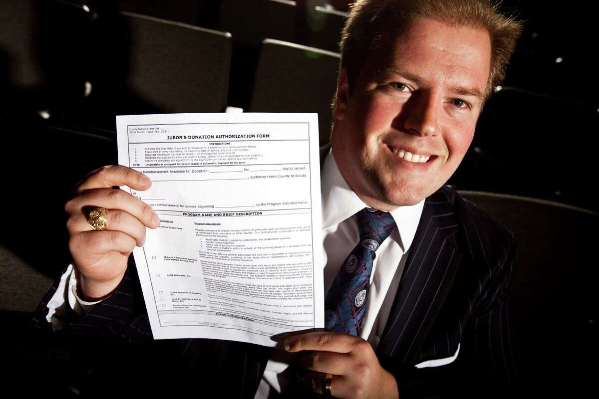 District Clerk Chris Daniel holds the form that lets prospective jurors donate their pay - a program that has sent more than $100,000 to charities this year.