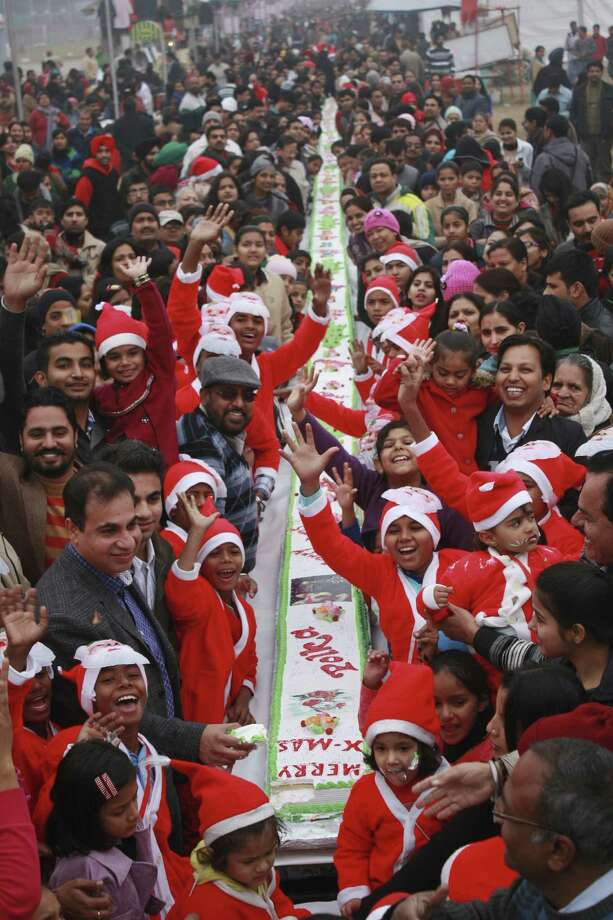 People react to cameras as they celebrate Christmas with a 151 feet Christmas cake at a shopping festival in Chandigarh, India, Tuesday, Dec. 25, 2012. Although Christians comprise only two percent of the population Christmas is a national holiday and is observed across the country as an occasion to celebrate. Photo: Kapil Sethi, Associated Press / AP