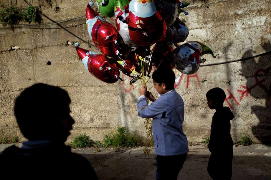 An Arab boy holds Santa Claus balloons to sell in the old market just outside the Church of the Annunciation, built on the site where Christians believe Mary was told by the angel Gabriel that she would give birth to Jesus Christ, in the town of Nazareth, northern Israel, Tuesday, Dec. 25, 2012. Photo: Ariel Schalit, Associated Press / AP