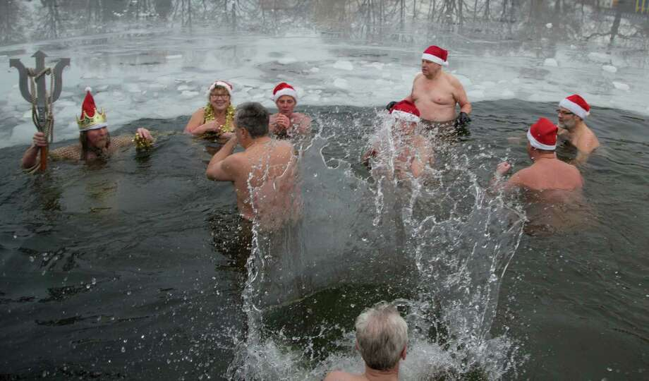 "Members of Berlin's swimming club ""Berliner Seehunde"" (Berlin seals) take a dip in the Orankesee lake during their traditional Christmas ice swimming session in Berlin on December 25, 2012. Photo: JOERG CARSTENSEN, AFP/Getty Images / DPA"