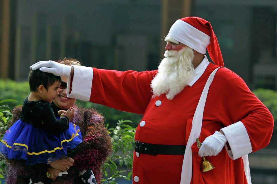 A man dressed as Santa Claus blesses a child at a Christmas Day party in Dhaka, Bangladesh, Tuesday, Dec. 25, 2012. Photo: A.M. Ahad, Associated Press / AP