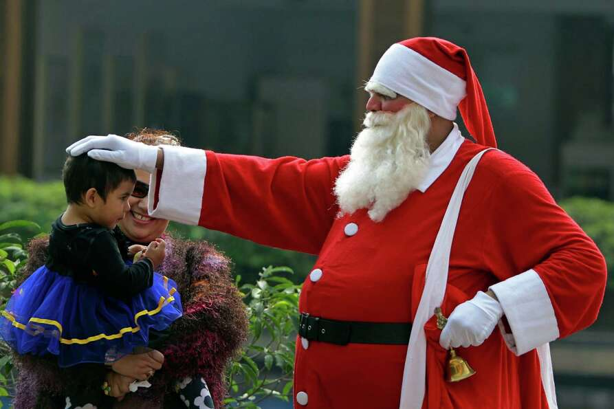 A man dressed as Santa Claus blesses a child at a Christmas Day party in Dhaka, Bangladesh, Tuesday,