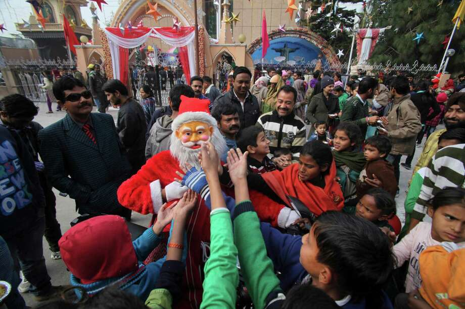 A person dressed as Santa Claus distributes sweets to children during Christmas celebrations outside Saint Mary's Garrison Church in Jammu, India, Tuesday, Dec. 25, 2012. Although Christians comprise only two percent of the population, Christmas is a national holiday and is observed across the country as an occasion to celebrate. Photo: Channi Anand, Associated Press / AP