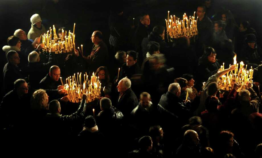 People light candles during a Christmas mass in the golden-domed Alexander Nevsky cathedral in central Sofia on December 25, 2012. Bulgaria, unlike some other fellow Orthodox countries, celebrates Christmas on December 25. Photo: NIKOLAY DOYCHINOV, AFP/Getty Images / AFP