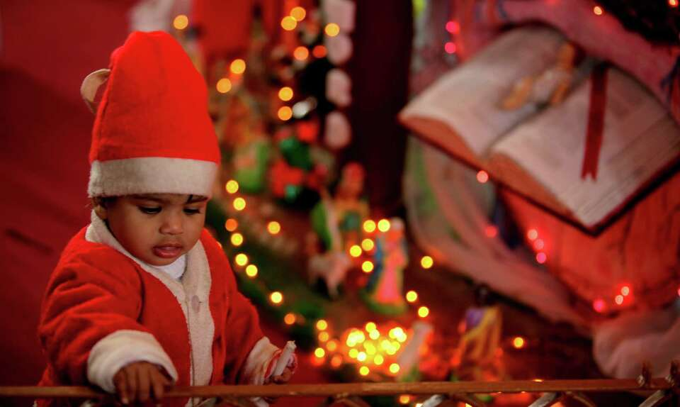 A young Indian child dressed as Santa Claus plays at a church, during Christmas celebrations in Jamm