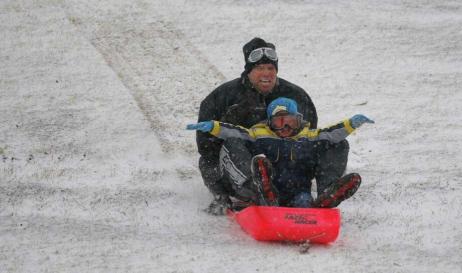Lucas Martinez and his dad, Nick, hit the hill at Trinity Park in Fort Worth, Texas, for Christmas Day fun in the snow, Tuesday, December 25, 2012. Photo: Ben Noey Jr, McClatchy-Tribune News Service / Fort Worth Star-Telegram