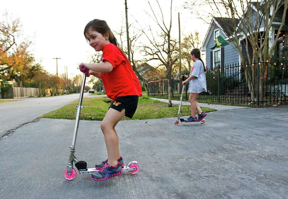 Chloe West, 4, plays on her new scooter, a Christmas gift, with her sister Ella West, 9, Tuesday, Dec. 25, 2012, outside their Houston Heights home in Houston.  Sunny skies and mild temperatures for Christmas afternoon were expected to give way to freezing temperatures overnight. Photo: Nick De La Torre, Houston Chronicle / © 2012  Houston Chronicle