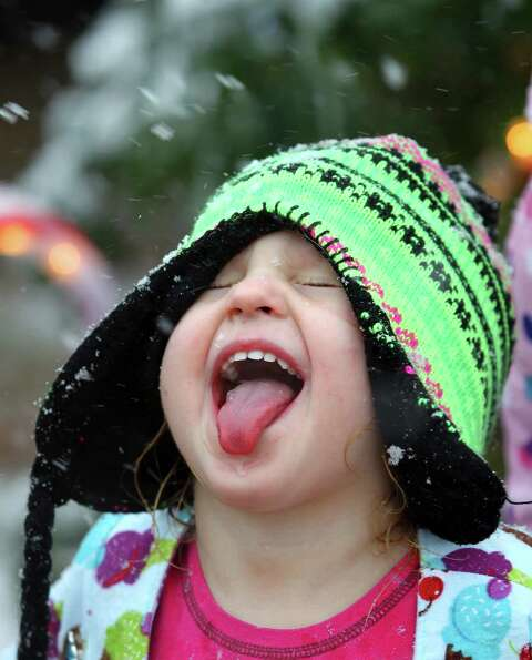 Iris Davis sticks her tongue out trying to catch snowflakes Tuesday, Dec. 25, 2012 after a strong wi