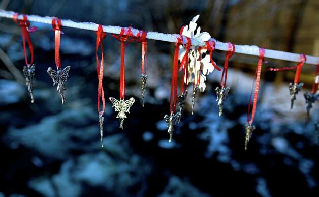 Angel pendants hang from a snow-covered string in Newtown, Conn. Tuesday, Dec. 25, 2012. People continue to visit memorials in the wake of the shootings after gunman Adam Lanza walked into Sandy Hook Elementary School in Newtown, Conn., Dec. 14, and opened fire, killing 26, including 20 children, before killing himself. Photo: Craig Ruttle, Associated Press / FR61802 AP