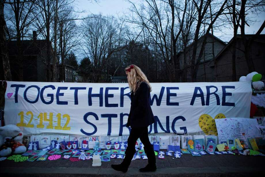 "A woman walks past a sign that reads ""Together we are Strong"" at a memorial for those killed in the school shooting at Sandy Hook Elementary School on December 24, 2012 in Newtown, Connecticut. Donations and letters are pouring in from across the country as the town tries to recover from the massacre. Photo: Andrew Burton, Getty Images / 2012 Getty Images"