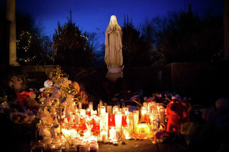 Candles left as a memorial for those killed in the school shooting at Sandy Hook Elementary School sit beneath a statue of the Virgin Mary on December 24, 2012 in Newtown, Connecticut. Donations and letters are pouring in from across the country as the town tries to recover from the massacre. Photo: Andrew Burton, Getty Images / 2012 Getty Images