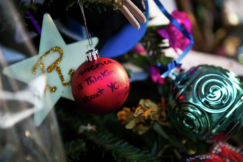 "A Christmas tree ornament reasds ""America is Thinking about you!"" at a memorial for those killed in the school shooting at Sandy Hook Elementary School on December 24, 2012 in Newtown, Connecticut. Donations and letters are pouring in from across the country as the town tries to recover from the massacre. Photo: Andrew Burton, Getty Images / 2012 Getty Images"