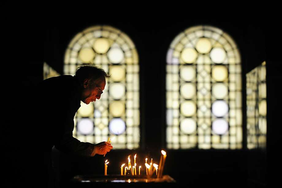A sexton collects candles during a Christmas mass in the golden-domed Alexander Nevsky cathedral in central Sofia on December 25, 2012. Bulgaria, unlike some other fellow Orthodox countries, celebrates Christmas on December 25. Photo: Nikolay Doychinov, AFP/Getty Images