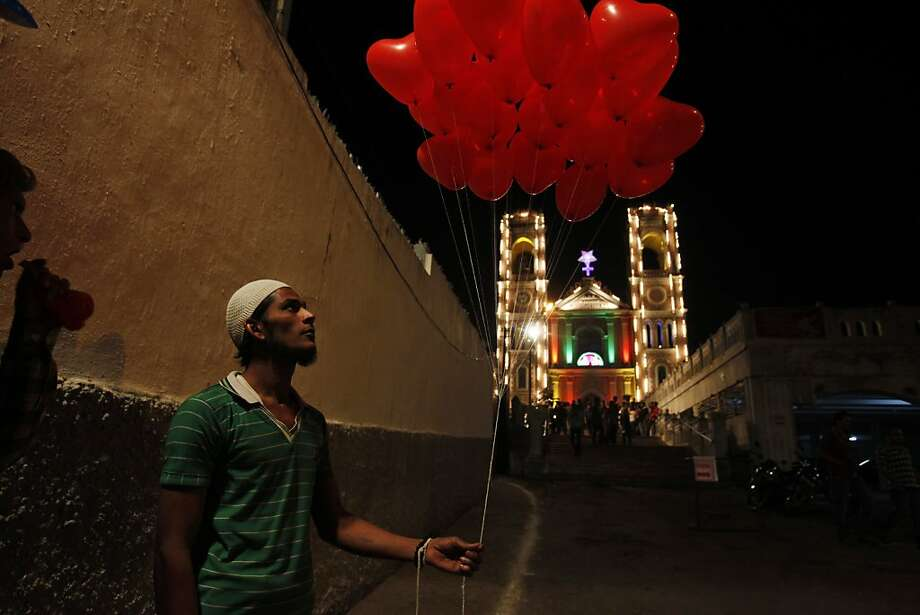 An Indian Muslim vendor sells balloons in front of St Joseph Cathedral during Christmas celebrations in Hyderabad, India, early Tuesday, Dec. 25, 2012. Although Christians comprise only two percent of the population Christmas is a national holiday and is observed across the country as an occasion to celebrate. Photo: Mahesh Kumar A, Associated Press