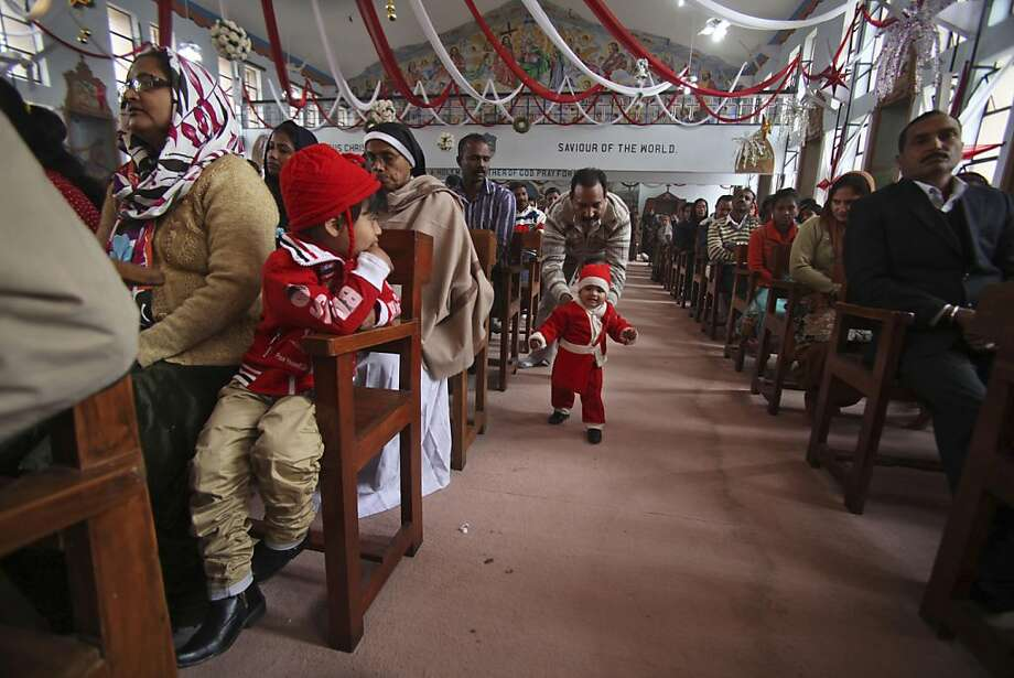 A child dressed in Santa Claus clothes walks during Christmas prayers at the Saint Mary's Garrison Church in Jammu, India, Tuesday, Dec. 25, 2012. Although Christians comprise only two percent of the population Christmas is a national holiday and is observed across the country as an occasion to celebrate. Photo: Channi Anand, Associated Press