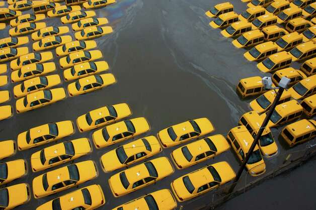 A parking lot full of yellow cabs is flooded as a result of superstorm Sandy on Tuesday, Oct. 30, 2012 in Hoboken, NJ. (AP Photo/Charles Sykes) Photo: Charles Sykes / FR170266 AP