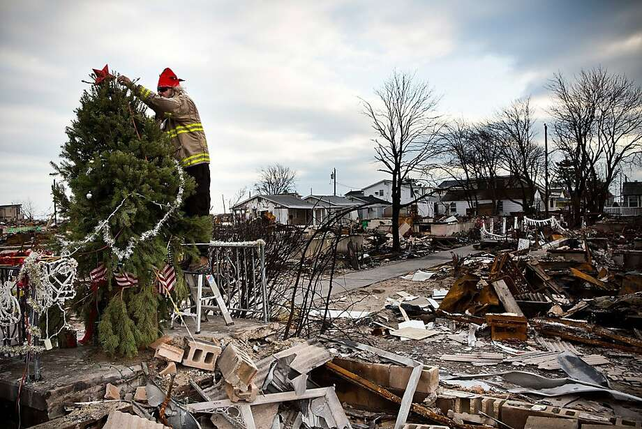 Edward ''Roaddawg'' Manley, a volunteer and honorary firefighter with the Point Breeze Volunteer Fire Department, places a star on top of a Christmas Tree in the Breezy Point neighborhood of the Borough of Queens on December 25, 2012 in New York City. Photo: Andrew Burton, Getty Images