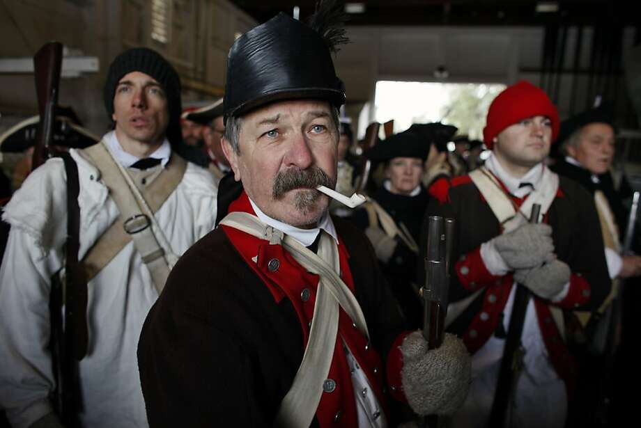 Revolutionary War re-enactor Pat Dunigan, center, of Pemberton NJ, smokes a pipe as he listens to instructions from a boat captain, Tuesday, Dec. 25, 2012, prior to the re-enactment of Washington crossing the Delaware River, in Washington Crossing, Pa. A strong current kept the re-enactors from making the crossing to New Jersey. Photo: Joseph Kaczmarek, Associated Press
