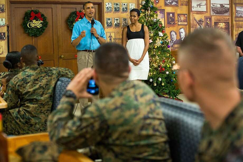 US President Barack Obama delivers remarks while First Lady Michelle Obama listens as they visited military personnel eating Christmas Dinner at Anderson Hall at Marine Corps Base Hawaii on December 25, 2012 in Kaneohe Bay, Hawaii. The president and his family spend the Christmas holiday in Hawaii, Obama's birthplace. Photo: Pool, Getty Images