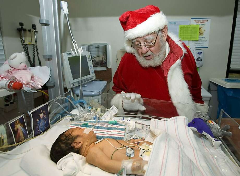 "In this Monday, Dec. 24, 2012 photo, Santa Claus whispers ""get well wishes"" to newborn baby girl Dalayna Molina, who is recovering from pneumonia, in the intensive care unit at Fountain Valley Hospital in Fountain Valley, Calif. Photo: Rose Palmisano, Associated Press"