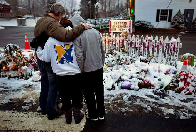 Members of the Rutter family of Sandy Hook, Conn., embrace early Christmas morning as they stand near memorials by the Sandy Hook firehouse in Newtown, Conn.,Tuesday, Dec. 25, 2012. People continue to visit memorials after gunman Adam Lanza walked into Sandy Hook Elementary School in Newtown, Conn., Dec. 14, and opened fire, killing 26, including 20 children, before killing himself.  (AP Photo/Craig Ruttle) Photo: Craig Ruttle, Associated Press