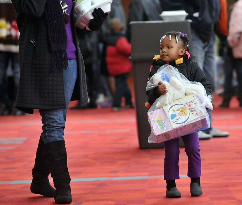 Nevaeh Pittman, 3, walks with her mother Kisha Pittman , of Marietta, after she got a toy during the Hosea Feed the Hungry and Homeless event at the Georgia World Congress Center Christmas Day, Tuesday, Dec. 25, 2012.  During the event, thousands of participants are served a meal, get clothing and toys, hair care and medical services, or had a chance to get a shower. Photo: Kent D. Johnson, Associated Press