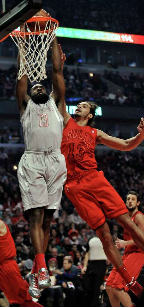 The Rockets' James Harden (13) dunks over the Bulls' Joakim Noah for two of his 26 points in the first quarter of Tuesday night's game at Chicago. Photo: PAUL BEATY, FRE / FR36811 AP