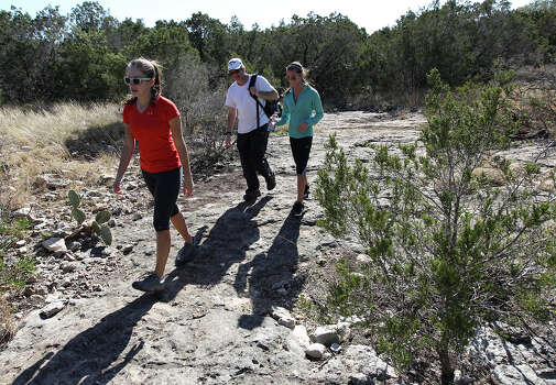 Alex (from left) with her father, Don, and her friend Rachel (last names withheld) take a hike on a trail at Government Canyon State Park on Tuesday, Dec. 25, 2012. The park remained open from Christmas until January 7th in an effort to attract more visitors as well as to validate funding for the parks by the legislature. The trio of hikers were amongst a small group of people who took advantage of the mild temperatures on Christmas day to visit the park. Photo: Kin Man Hui, San Antonio Express-News / ©2012 San Antonio Express-News
