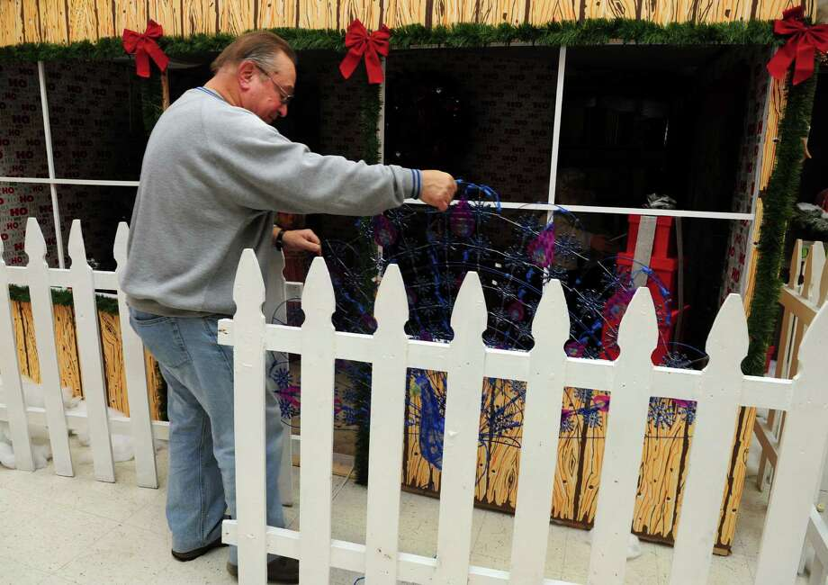 Mike Marella sets up the Christmas Village, run by the Bridgeport Police Athletic League (PAL), Tuesday, Nov. 27, 2012 in Trumbull, Conn.  The village is opening for the season on Saturday. Photo: Autumn Driscoll / Connecticut Post