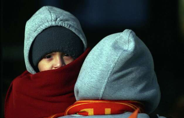 Ana Rodriguez carries son Yan Luna, 3, as they weather the cold to eat at a nearby restaurant in west Houston on Wednesday, Dec. 26, 2012, in Houston. Photo: Mayra Beltran, Houston Chronicle / © 2012 Houston Chronicle
