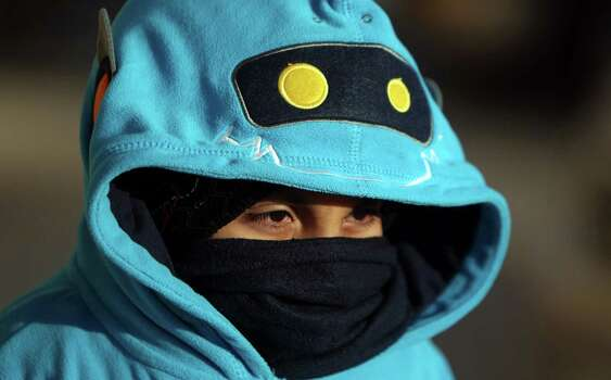 Ken Luna, 8, weathers the cold with his mother as they walk to a nearby restaurant in west Houston on Wednesday, Dec. 26, 2012, in Houston. Photo: Mayra Beltran, Houston Chronicle / © 2012 Houston Chronicle