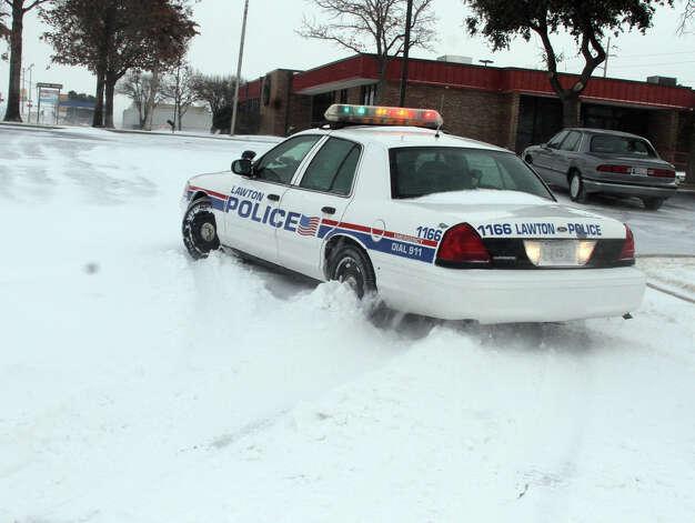 A Lawton, Okla., police cruiser tries to navigate the snow as blizzard conditions hit southwest Oklahoma at midday Tuesday, Dec. 25, 2012. (AP Photo/The Lawton Constitution, Brandon Neris) Photo: Brandon Neris, MBR / The Lawton Constitution