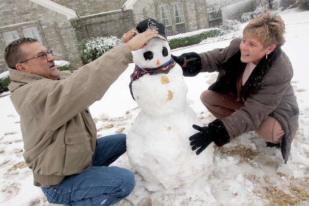 Tommy and Cindy Huddleston put the finishing touches on their snowman in Paris, Texas Tuesday, Dec. 25, 2012 after a strong winter system dropped inches of rain and snow on most of North East Texas. (AP Photo/The Paris News, Sam Craft) Photo: Sam Craft, MBR / The Paris News