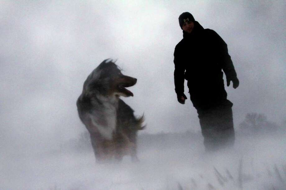 Tucker is unfazed as he leads his owner, Zach Stead, through high winds, blowing snow and freezing temperatures Thursday, Dec. 20, 2012 in Springfield, Ill. Photo: Seth Perlman, Associated Press / AP