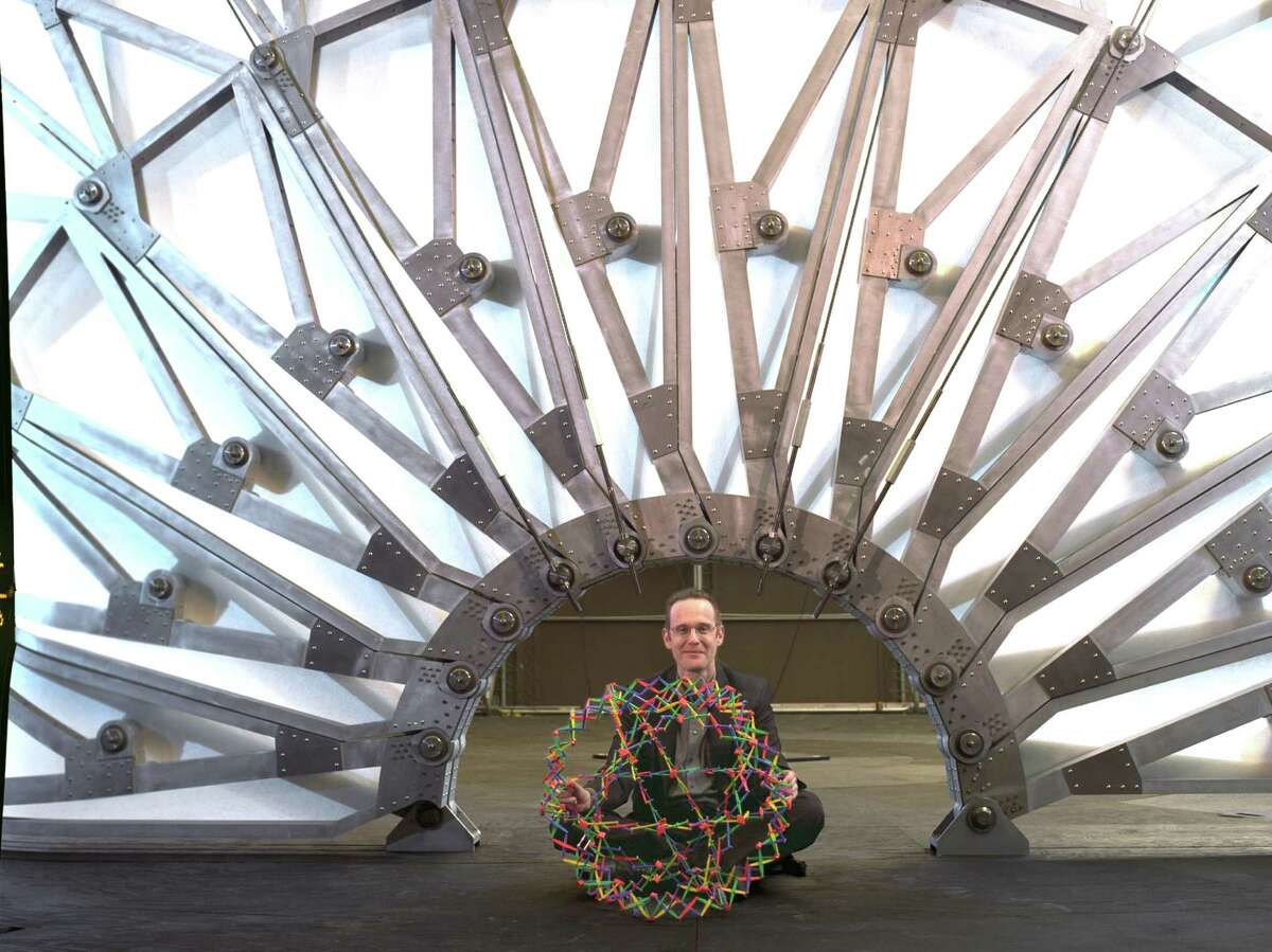 Former Greenwich resident Chuck Hoberman holds the Hoberman Sphere, a toy he invented that was on display recently at the opening of the Museum of Mathematics in New York City, as he sits under his Hoberman Arch, which he built for the 2002 Winter Olympics in Salt Lake City, Utah.
