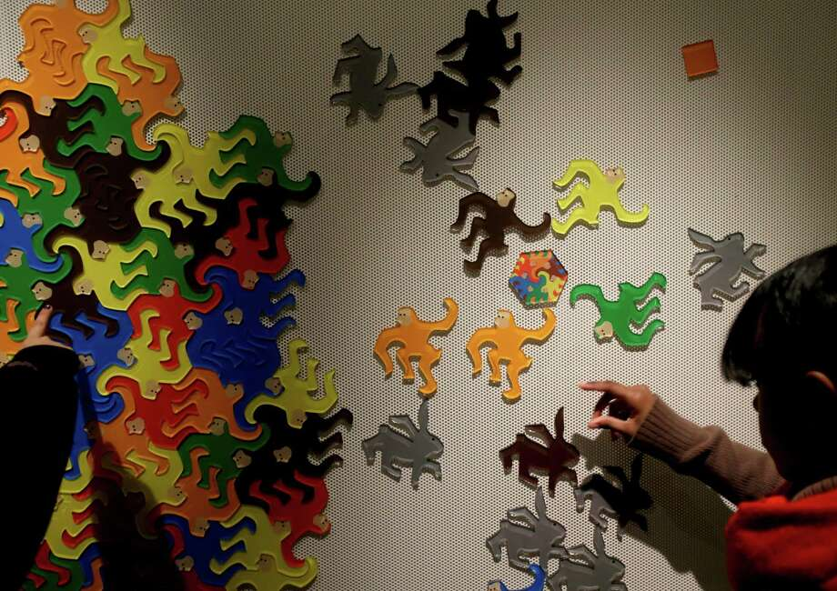 "Students play with interlocking shapes at a ""Tessellation Station"" at the new National Museum of Mathematics in New York, Monday, Dec. 17, 2012. The museum is aimed at kids aged 8 to 13, and curators have given the place a playground feel. The 40 exhibits include a ""wall of fire"" made up of laser lights that teaches kids about geometry and a square-wheeled tricycle that still manages to produce a smooth ride thanks to a wavy track. Photo: Seth Wenig, AP / AP"
